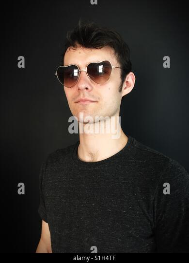 A young man wearing heart shaped sunglasses. - Stock Image