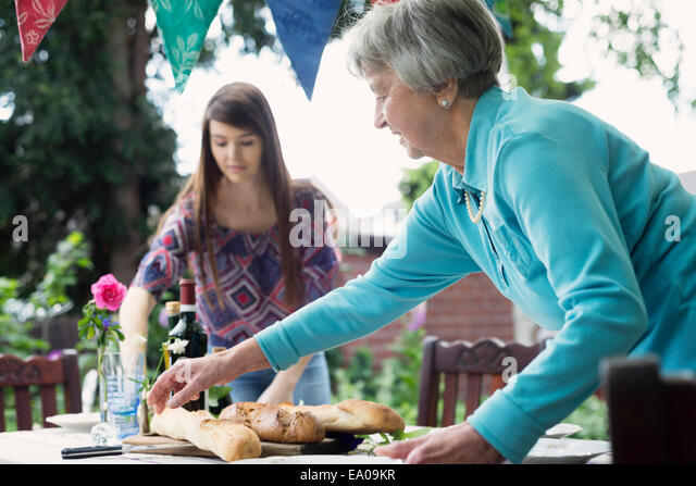 Senior woman setting the table outdoors - Stock Image