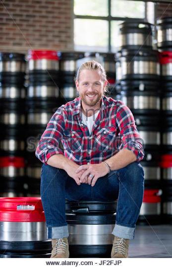 Portrait Of Brewery Worker Sitting On Beer Kegs In Store Room - Stock Image