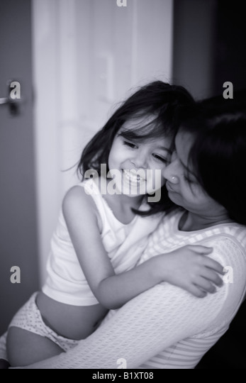 Mixed race daughter and Indian mother girl aged five in her mother's arms - Stock-Bilder