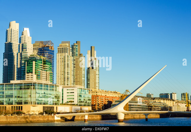 Skyscraper and the Women's Bridge in the upscale neighborhood of Puerto Madero in Buenos Aires - Stock Image