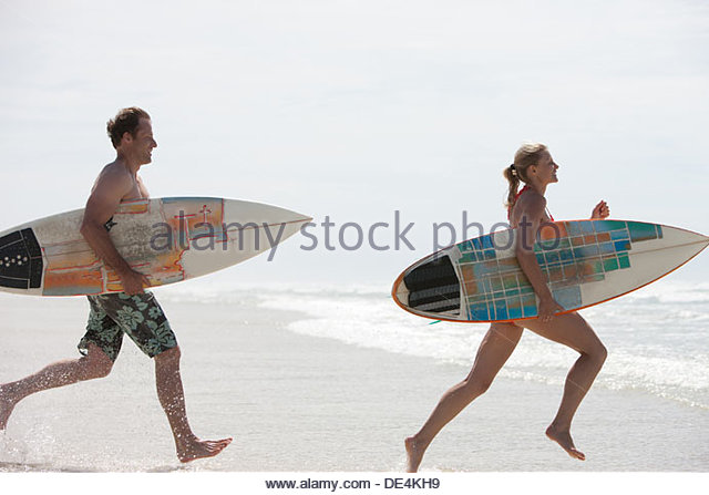 Couple with surfboards running on beach - Stock-Bilder