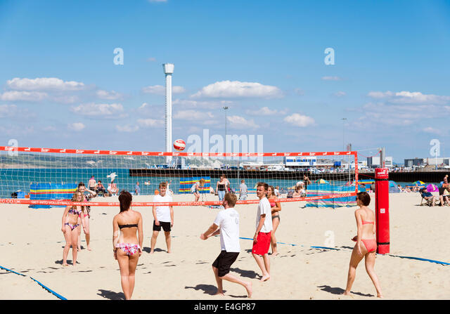 People playing beach volleyball at Weymouth, Dorset, UK. - Stock Image