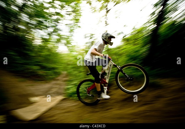A young man downhill bicycling outdoor. - Stock Image
