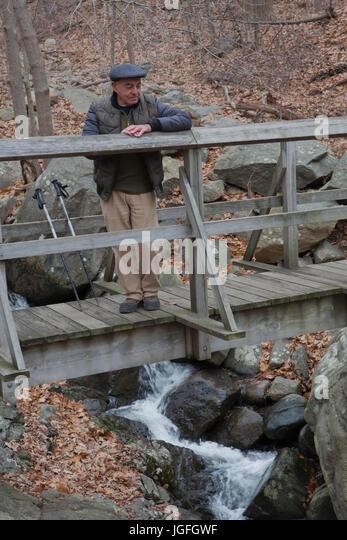 Hispanic man relaxing on footbridge - Stock Image