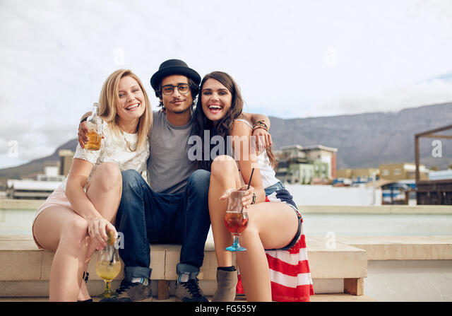 Portrait of best friends hanging out on a roof with drinks. Young man and women partying outdoors. - Stock Image