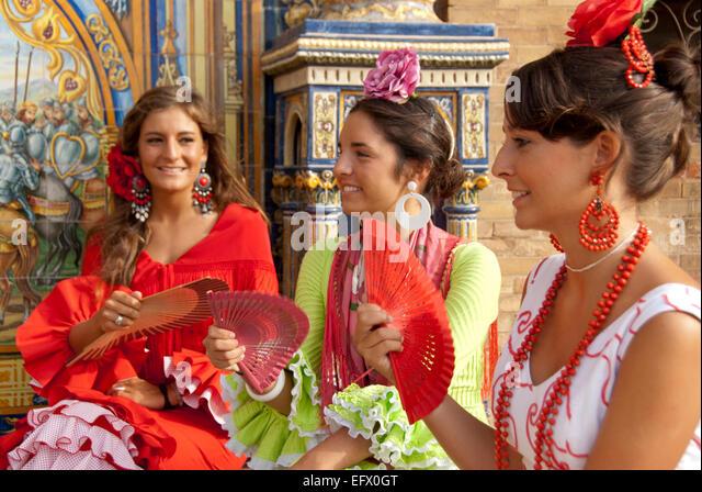 Seville fair Feria de Abril Sevilla Spring Fair Three friends in Flamenco dresses Sevillanas Fans Traditional attire - Stock Image