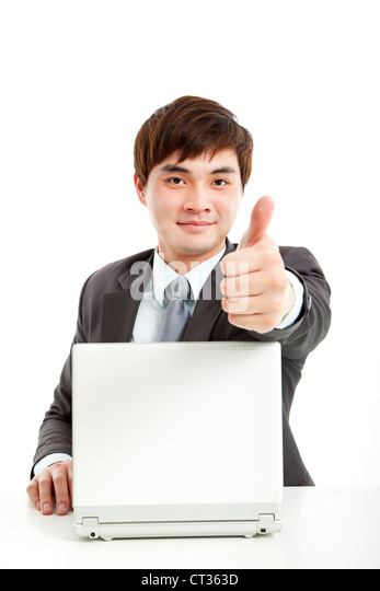 successful businessman working with computer and showing thumb up - Stock Image