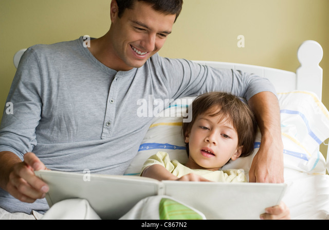 Father and son reading story together - Stock Image