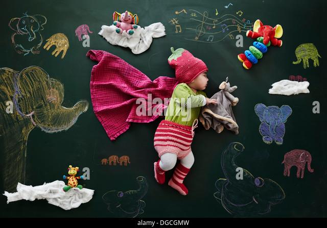 Baby girl sleeping against drawings on blackboard, overhead view - Stock-Bilder