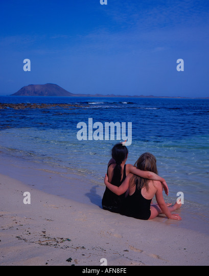Fuerteventura two girls sitting at the beach. Photo by Willy Matheisl - Stock Image