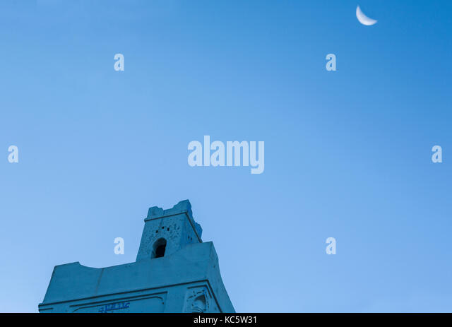 Sunrise silhouette of Mosque in Chefchaouen with moon, Morocco - Stock Image