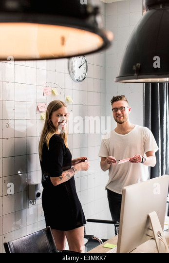 Portrait of young business people discussing ideas over adhesive notes in new office - Stock Image