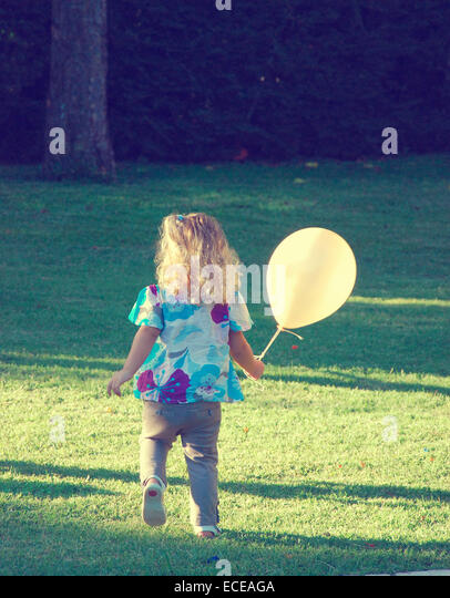 Argentina, Buenos Aires, Girl holding balloon at birthday party - Stock Image