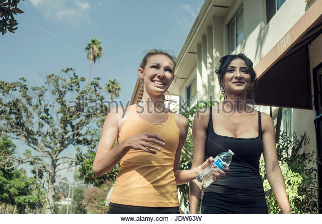 Two young women, walking together, smiling, low angle view - Stock-Bilder