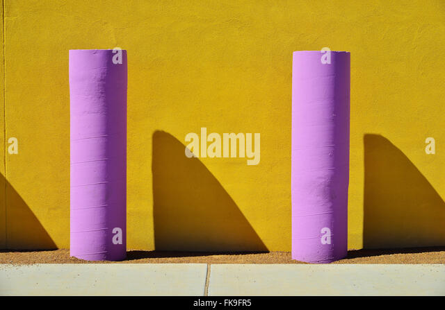 Colored concrete poles and contrasting colored walls - Stock Image