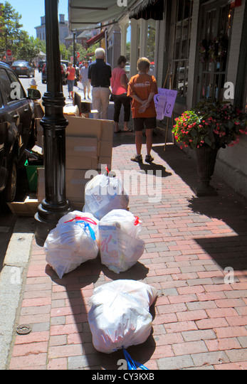 New Hampshire Portsmouth Market Street plastic trash bags businesses pick-up sidewalk curb curbside - Stock Image