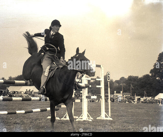 1950s, historical, a female equestrian rider jumps over a three bar fence at the Bucks County Show ground at Weedon - Stock Image