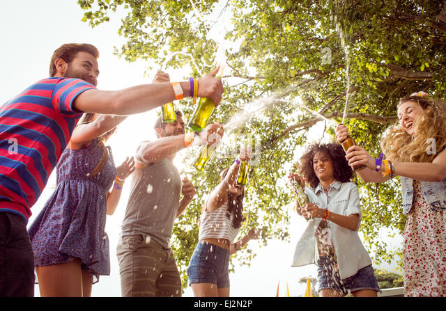 Happy hipsters spraying beer bottles - Stock Image