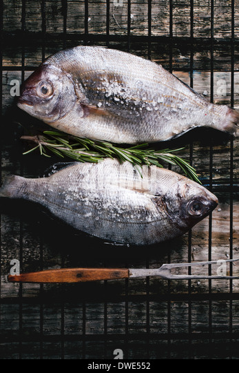 Top view on tow raw dorado fish with rosemary and sea salt on grill over old wooden table. See series - Stock Image