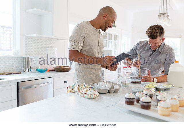Male couple using digital tablet recipe for baking in kitchen - Stock Image