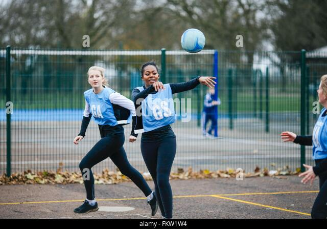 Female netball team playing match on netball court - Stock Image