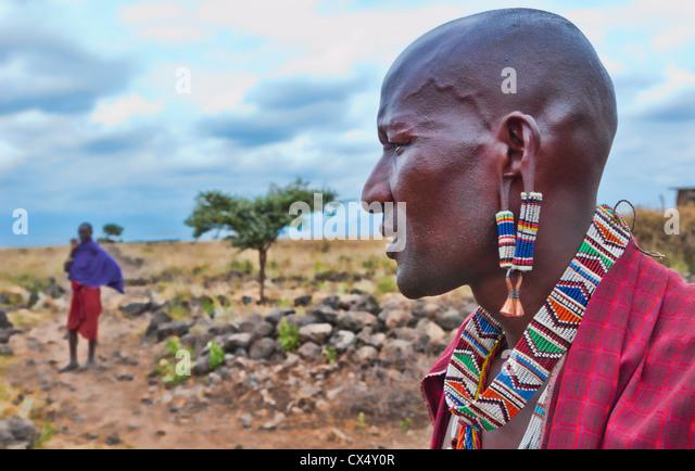 Kenya Africa Amboseli Maasai tribe village Masai man in red costume dress and beads close up of jewelry in remote - Stock-Bilder