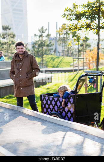 Sweden, Skane, Malmo, Father driving son (6-7) in urban park - Stock Image