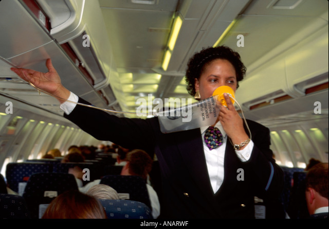 New Jersey Newark Airport KIWI International Airlines Black woman attendant safety demonstration oxygen mask - Stock Image
