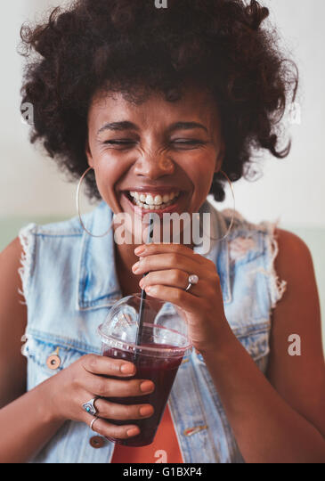 Close up portrait of cheerful young woman drinking fresh fruit juice and smiling. Happy young african female model - Stock Image