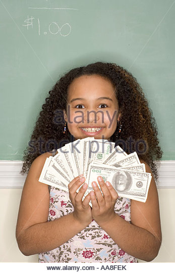 Young African girl holding fake money - Stock Image