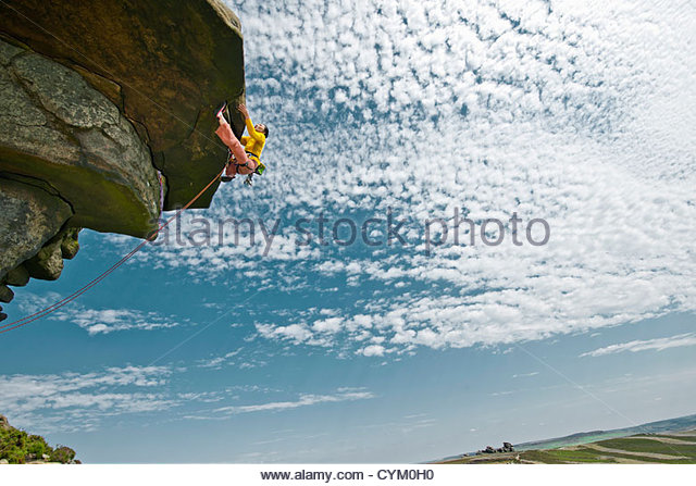 Rock climber scaling rock formation - Stock Image