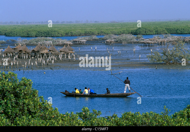 Canoe passing storage houses at Joal-Fadiouth, Senegal, Africa - Stock-Bilder