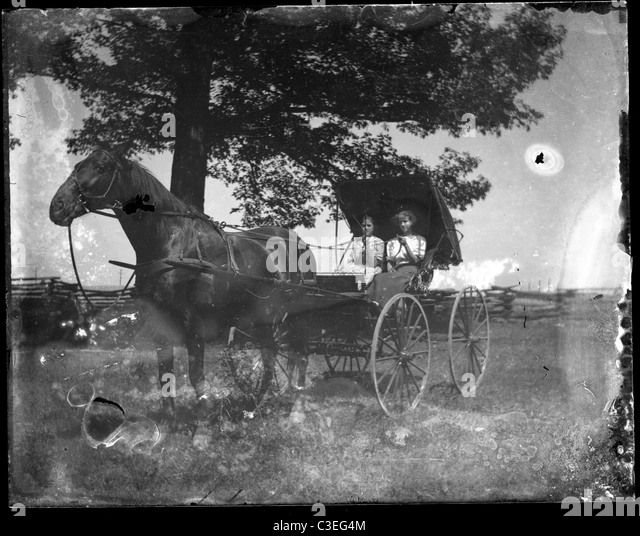 two women sitting in a horse and buggy dirt street road house transportation 19th century 1890s - Stock-Bilder