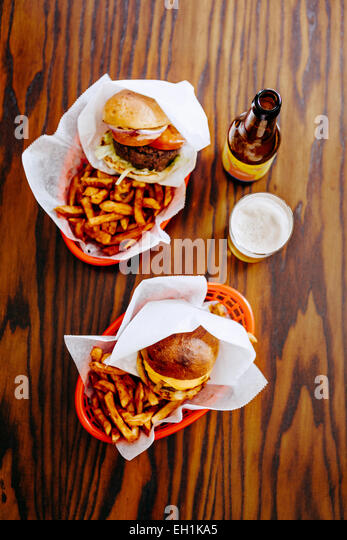 Directly above shot of fast foods served with beer on restaurant table - Stock Image