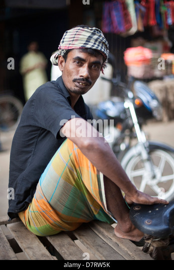 A cart puller at rest near the Chowk Bazaar, Dhaka, Bangladesh - Stock Image