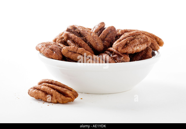 A bowl of cinnamon spiced pecans with white background cutout - Stock Image