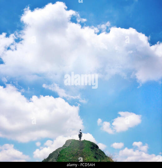 Low Angle View Of Woman Walking Up Rock Against Blue Sky And Clouds - Stock Image