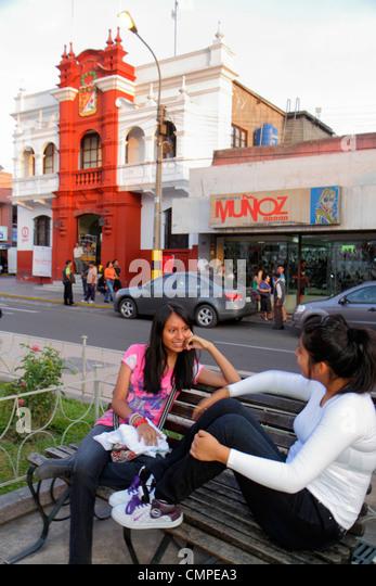 Peru Tacna Avenida San Martin Plaza de Armas public square urban park Hispanic girl teen sitting talking friends - Stock Image