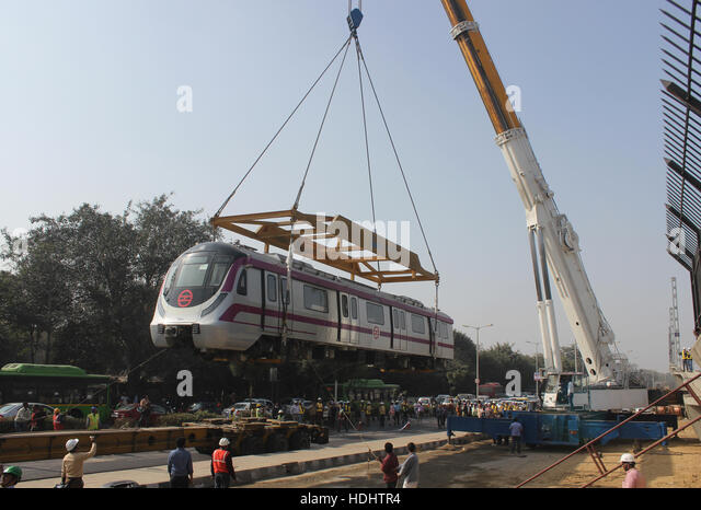 New Delhi, India. 12th Dec, 2016. Unloading of new metro train on track the help of cranes and trailers near under - Stock Image