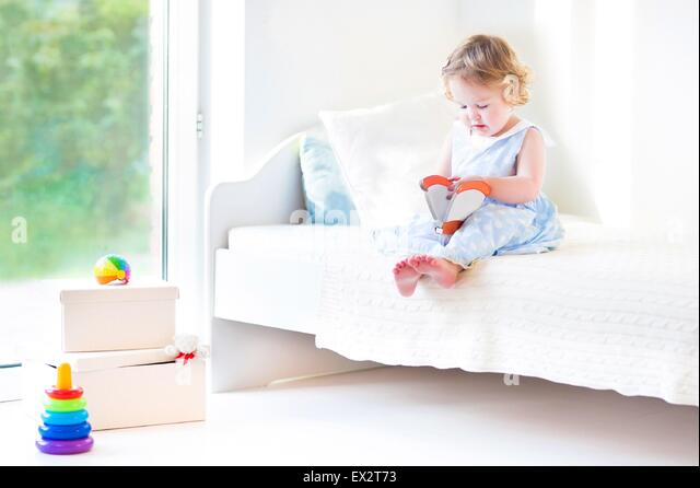 Beautiful curly toddler girl reading a book sitting on a white bed next to a big window with garden view - Stock Image
