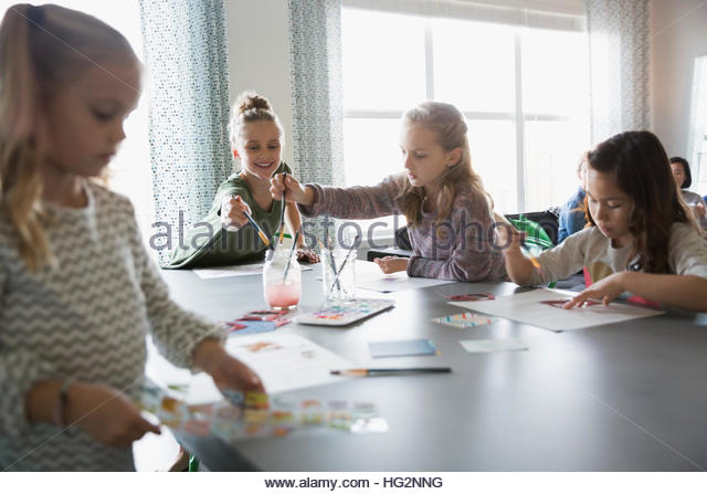 Girls enjoying play date painting at dining room table - Stock Image