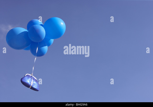 Blue purse flying with balloons - Stock Image