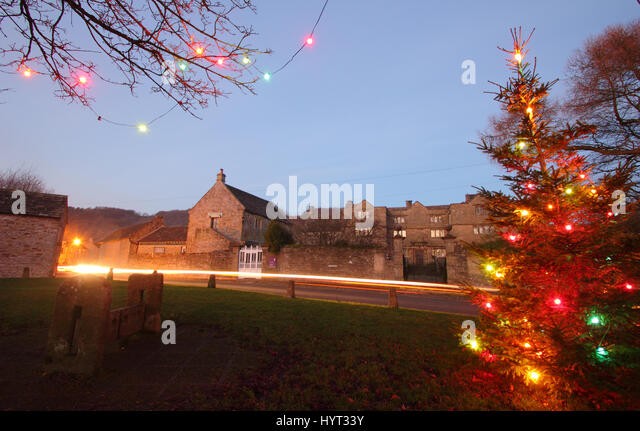 Christmas decorations by the wooden stocks opposite Eyam Hall (pictured) in Eyam; the pretty and historic 'plague - Stock Image