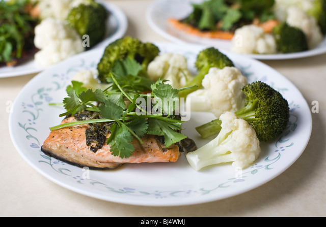 Gourmet meal of grilled salmon, broccoli, and cauliflower. - Stock Image