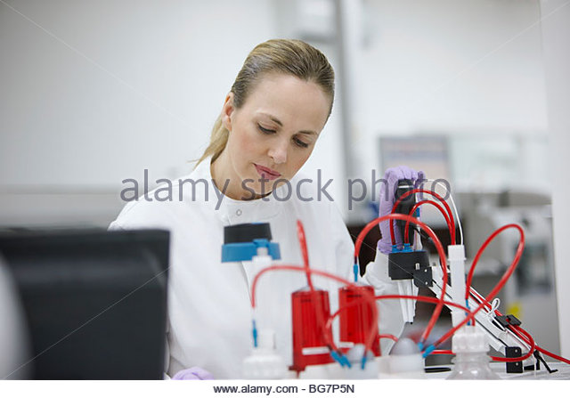 Scientist working with equipment in laboratory - Stock Image