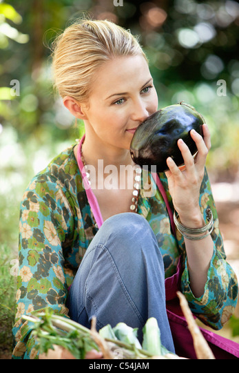 Smiling woman smelling eggplant - Stock Image