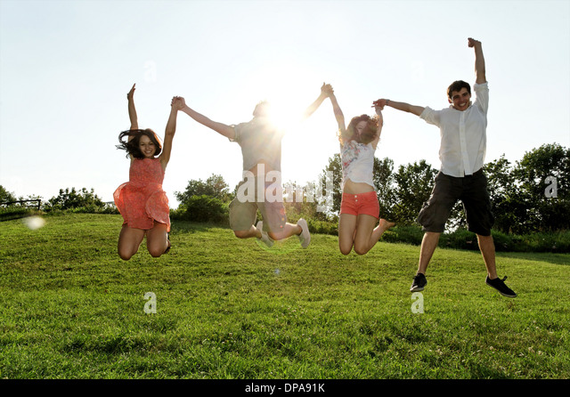 Group of young adults jumping mid air in field - Stock-Bilder