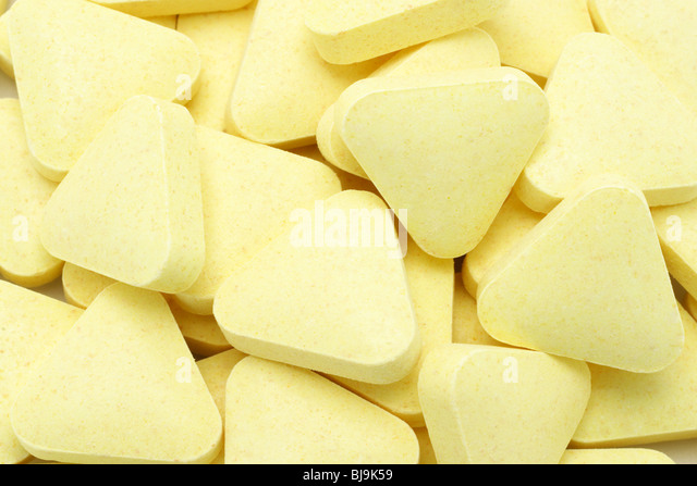 Yellow color triangular shape multi vitamin tablets background - Stock-Bilder