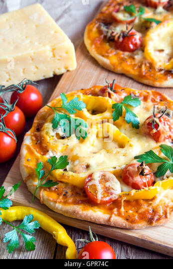 Vegetable pizza and ingredients on wooden cuting board - Stock Image